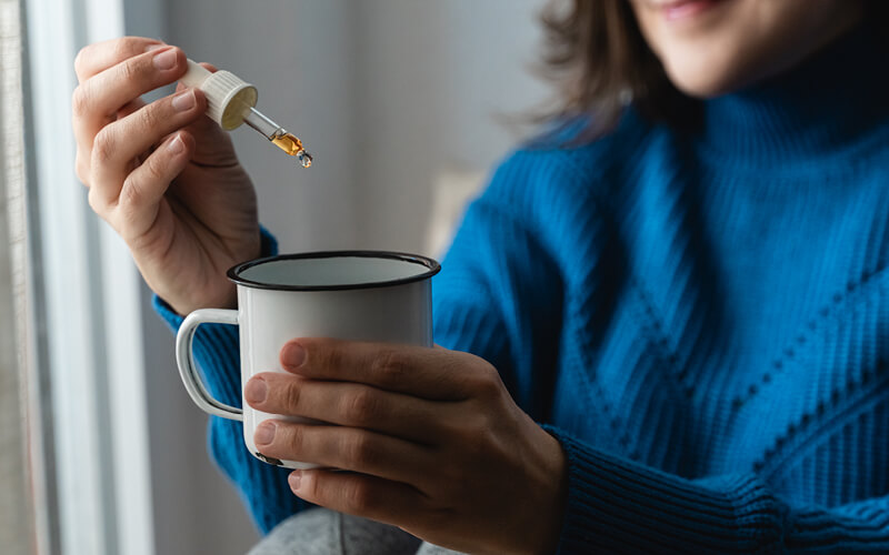 Woman adding drops of cannabis tincture to her coffee