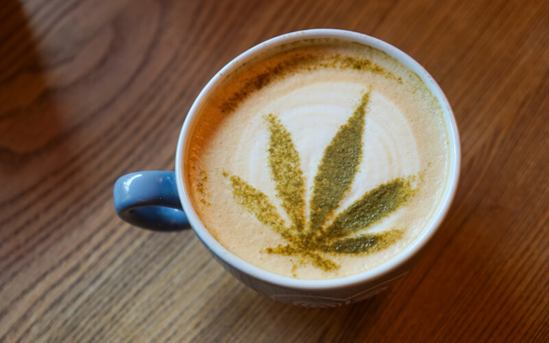 Cup of coffee topped with ground cannabis.