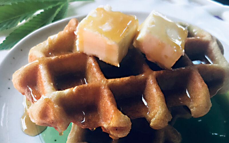 A waffle topped with butter and cannabis-infused liquor