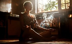 Woman smoking cannabis and practicing yoga inside an apartment.
