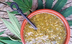 Bowl of salsa surrounded by cannabis leaves.