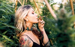 Woman standing inside a cannabis grow smoking a joint