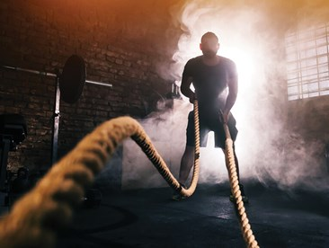 Man doing rope exercises while surrounded by cannabis smoke.