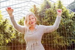 Photo of Watermelon aka Mary Jean Dunsdon posing in front of a cannabis grow.